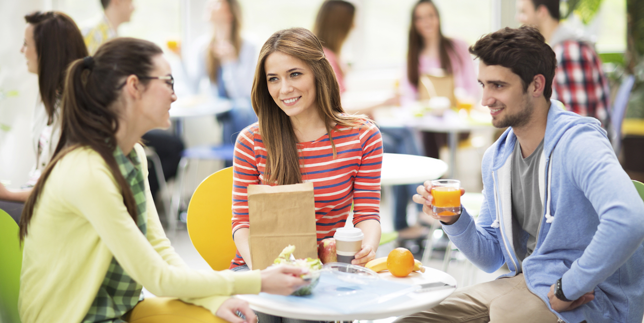 Group of students in a cafeteria. Focus is on foreground, on three young adults communicating.